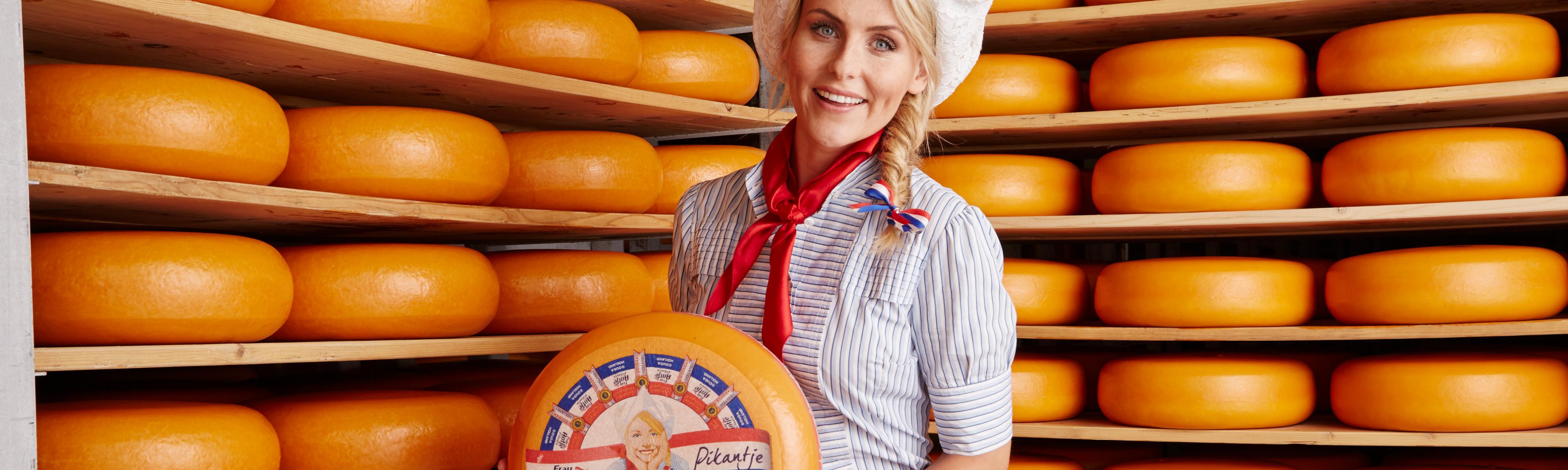 Kaasmeisje met hele kaas tussen de kazen