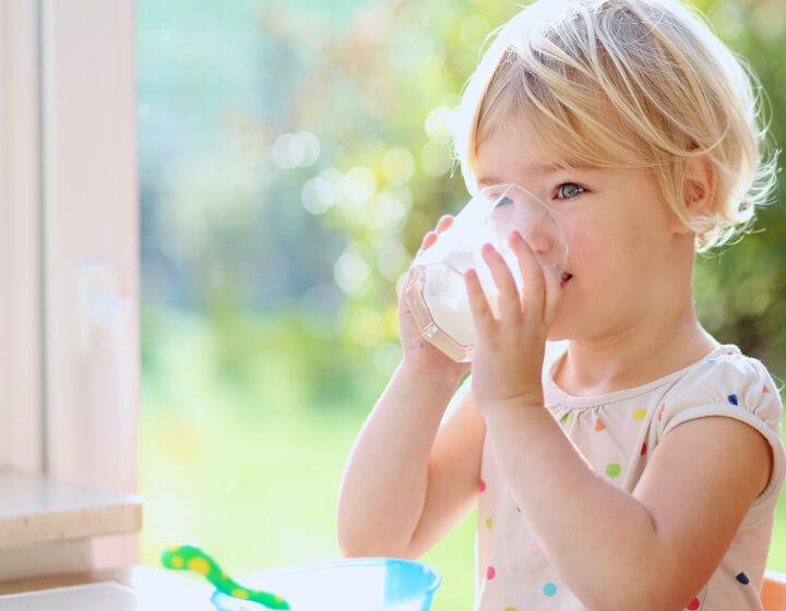 Meisje dat melk drinkt uit een glas