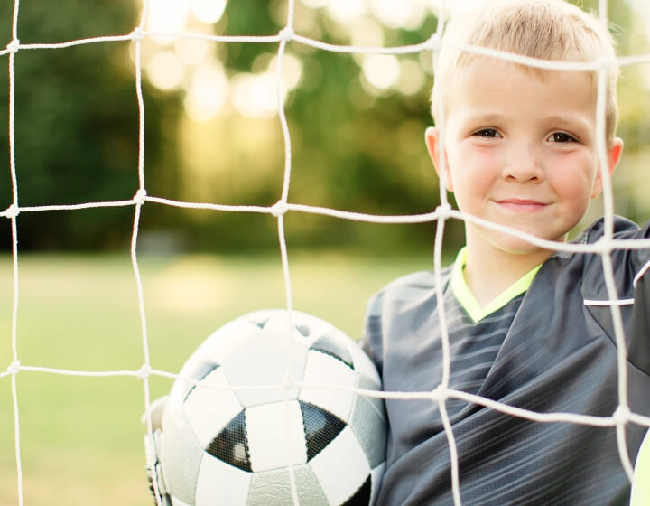 Jongetje in het voetbaldoel met voetbal