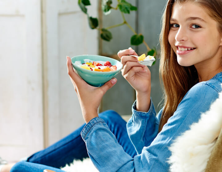 Meisje die een bakje yoghurt met fruit eet