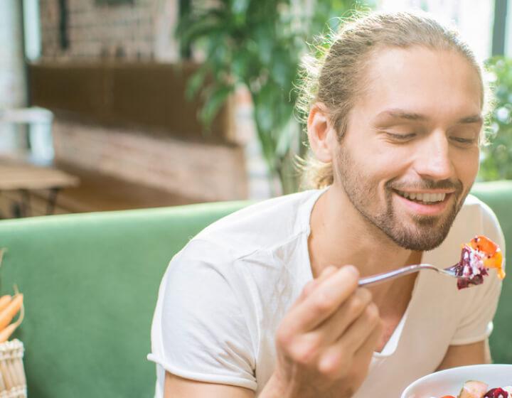 Man die een vork vasthoudt met eten