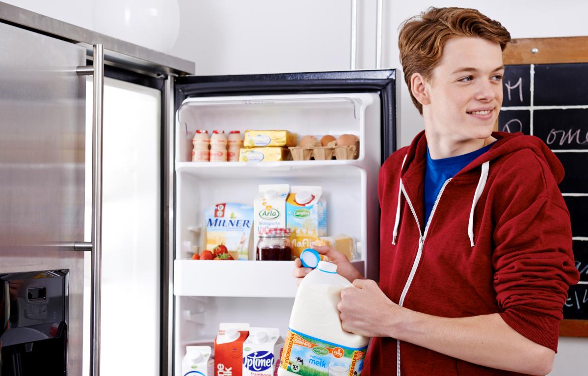 Jongen die melkpak uit de koelkast pakt