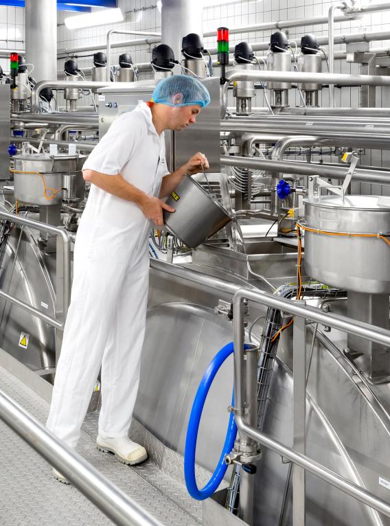 Man aan het werk in de zuivelfabriek