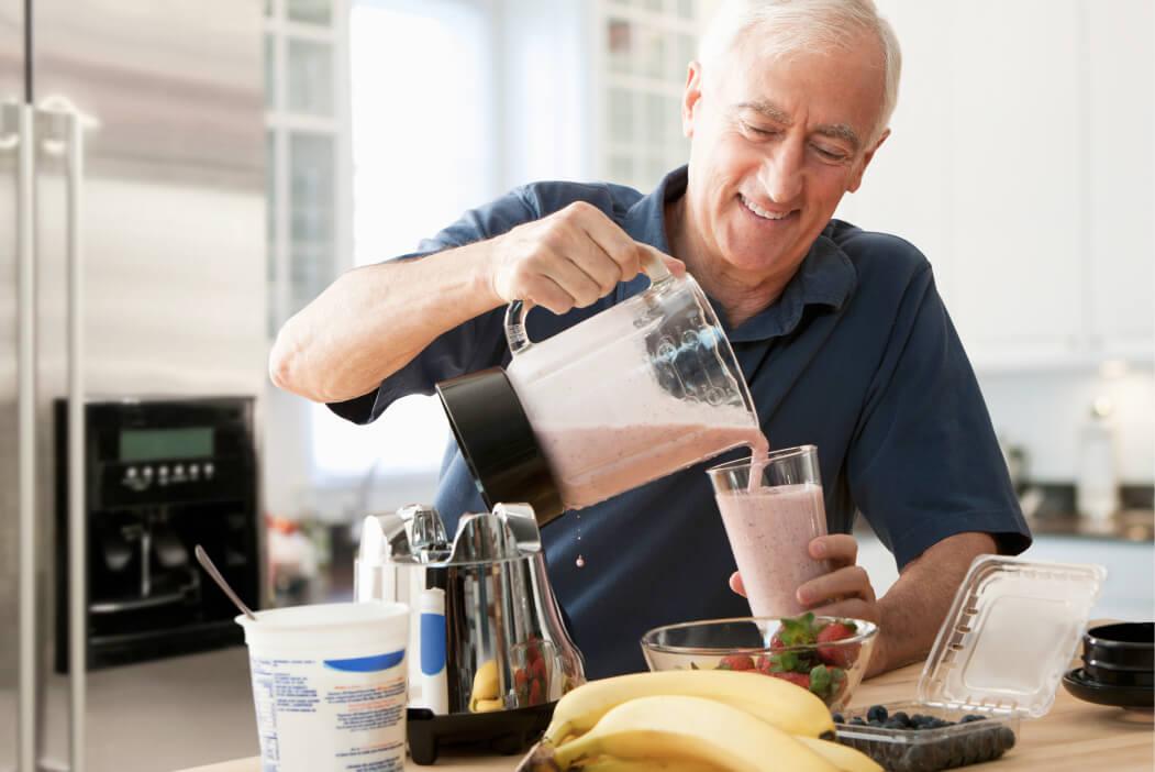Oudere man die smoothie inschenkt in glas