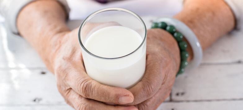 Iemand die glas melk vasthoudt met twee handen