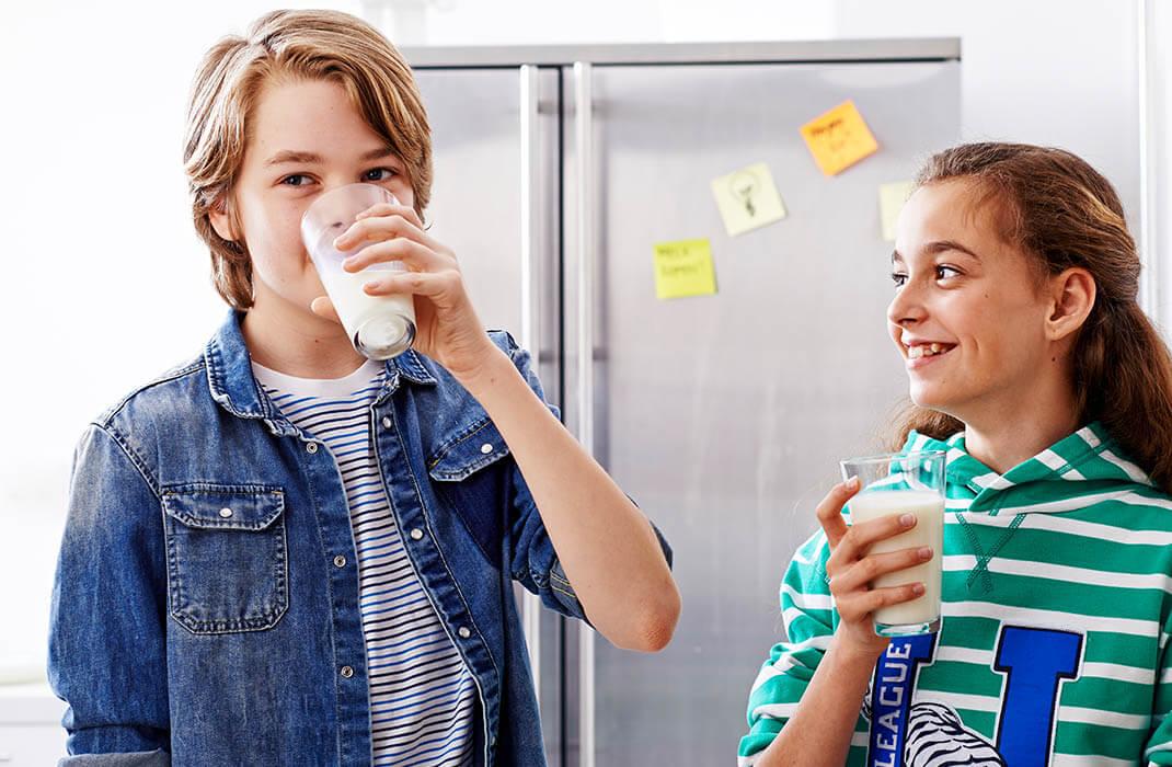 Jongen en meisje die allebei een glas melk drinken