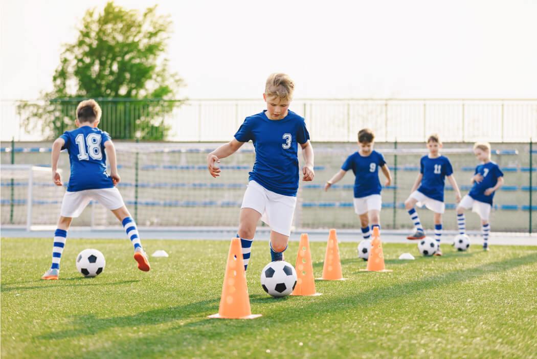 Kinderen dribbelen met voetbal tussen pylonen door