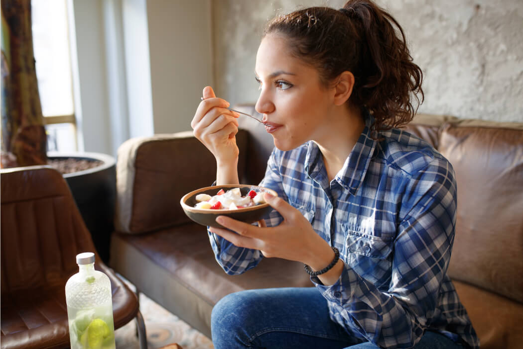 Vrouw die bakje yoghurt met fruit eet